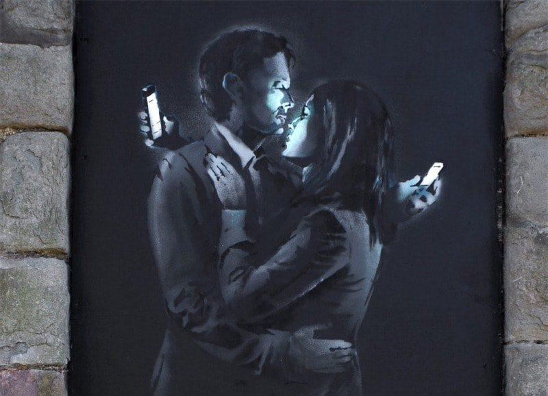 На фото мурал «Mobile Lovers» нарисованный в 2014 году, в Бристоле, стрит-арт художником Banksy.